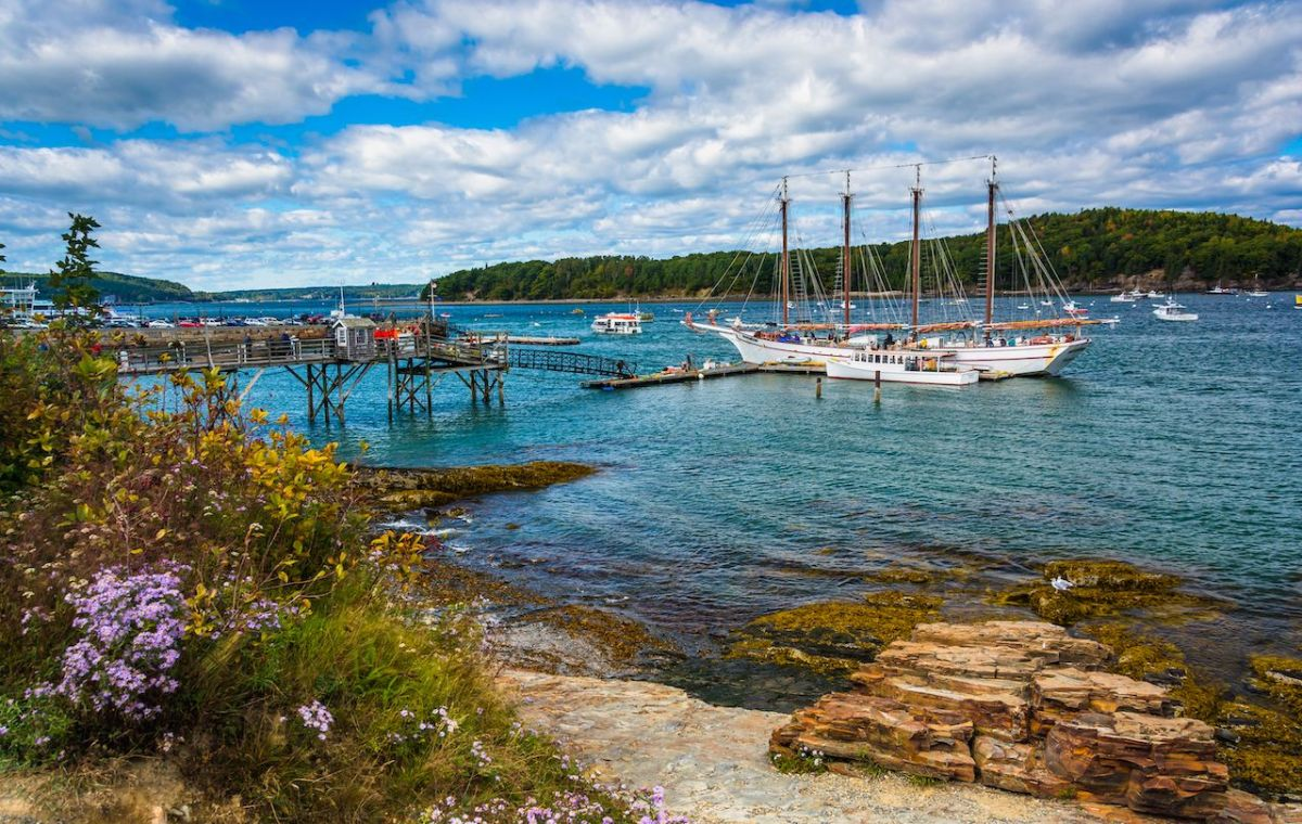 Rocky coast and view of boats in the harbor at Bar Harbor, Maine.