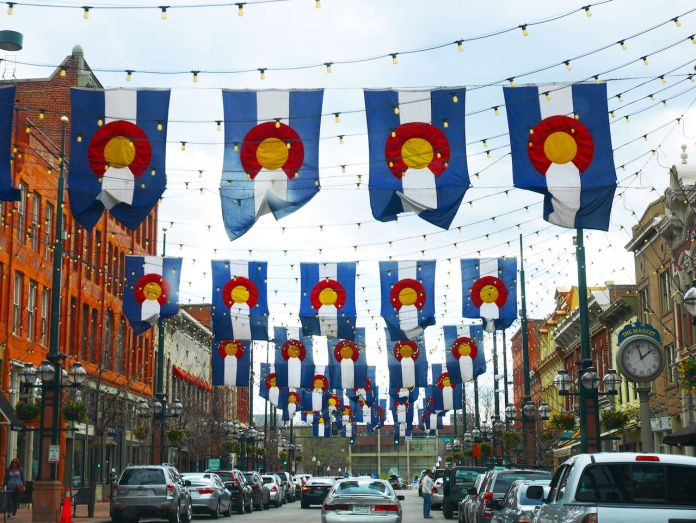 Traffic in downtown Denver with cars and hanging state flags