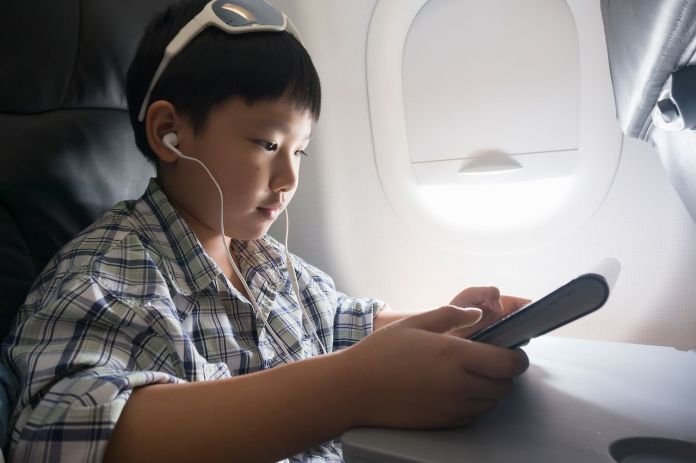 Child using a tablet on a plane