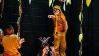 student in tiger costume pointing
