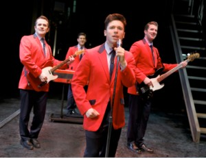 Quartet in red jackets singing with instruments