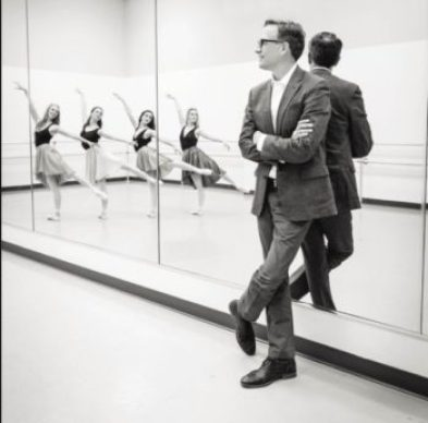 Man standing against mirror while ballerinas practice