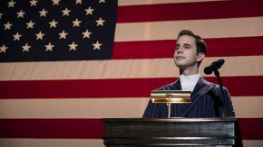 man at podium in front of an American flag
