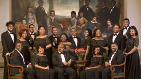 Fisk Jubilee Singers seated in front of painting