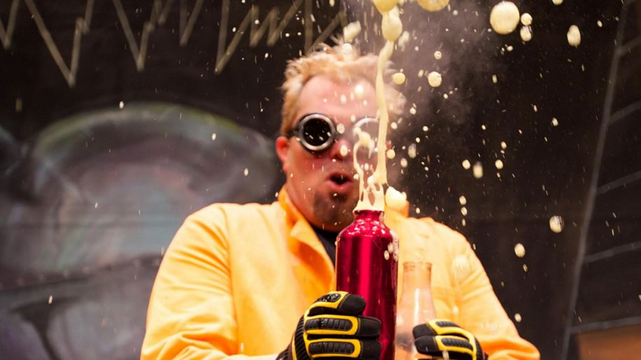 scientist with goggles holding a bottle exploding with fizz