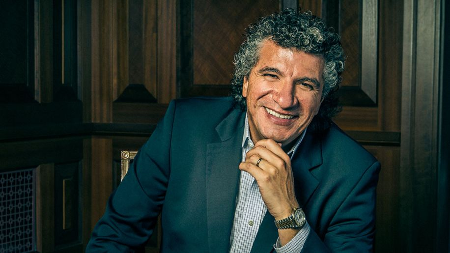 Giancarlo Guerrero smiling with his hand on his chin