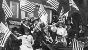 black and white photo of suffragettes blowing horns and waving flags