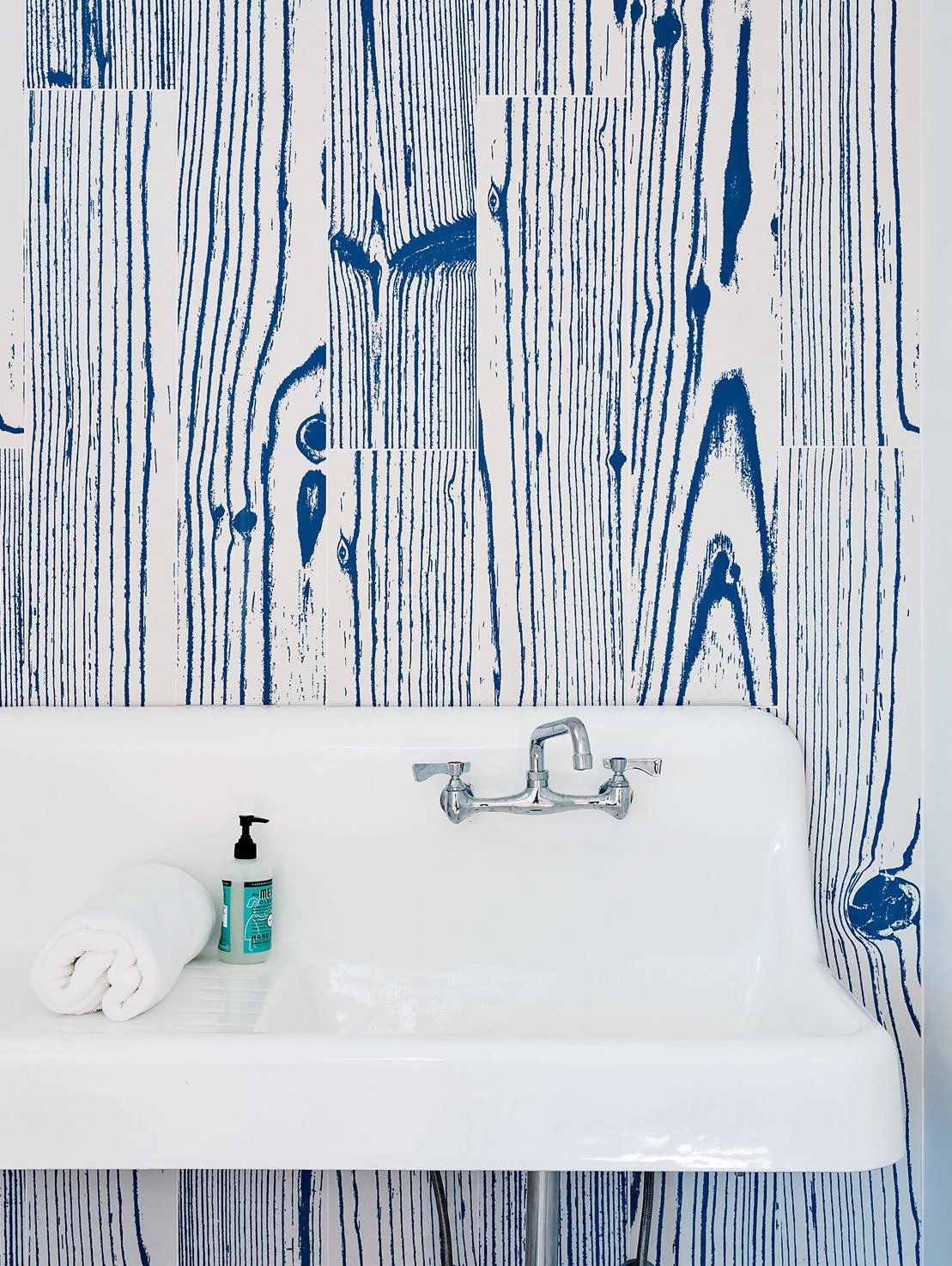 White-and-blue, wood-grain–patterned UonUon tiles by 14oraitaliana line the bathroom walls in a loft above the garage.