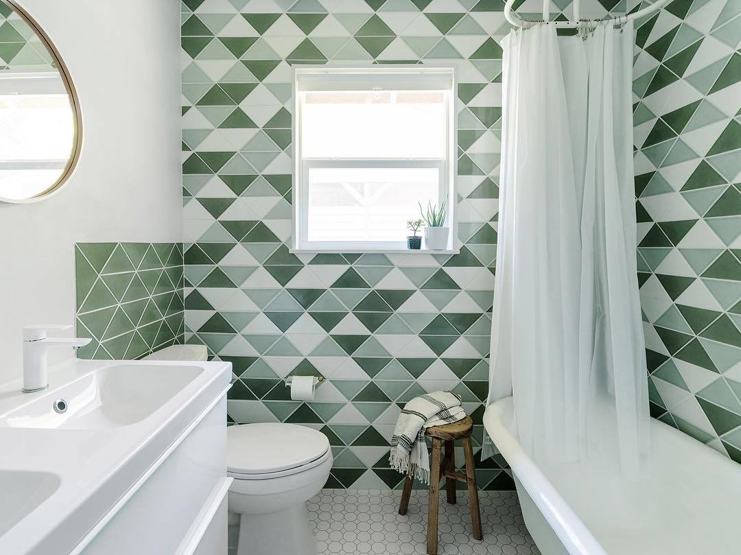 After completing the renovation of his home in Austin, Texas, photographer and designer Chase Daniel shared the final result of his bathroom. He covered the walls with triangle tiles from Fireclay Tile in the shades of Rosemary, Salton Sea, and Frost.