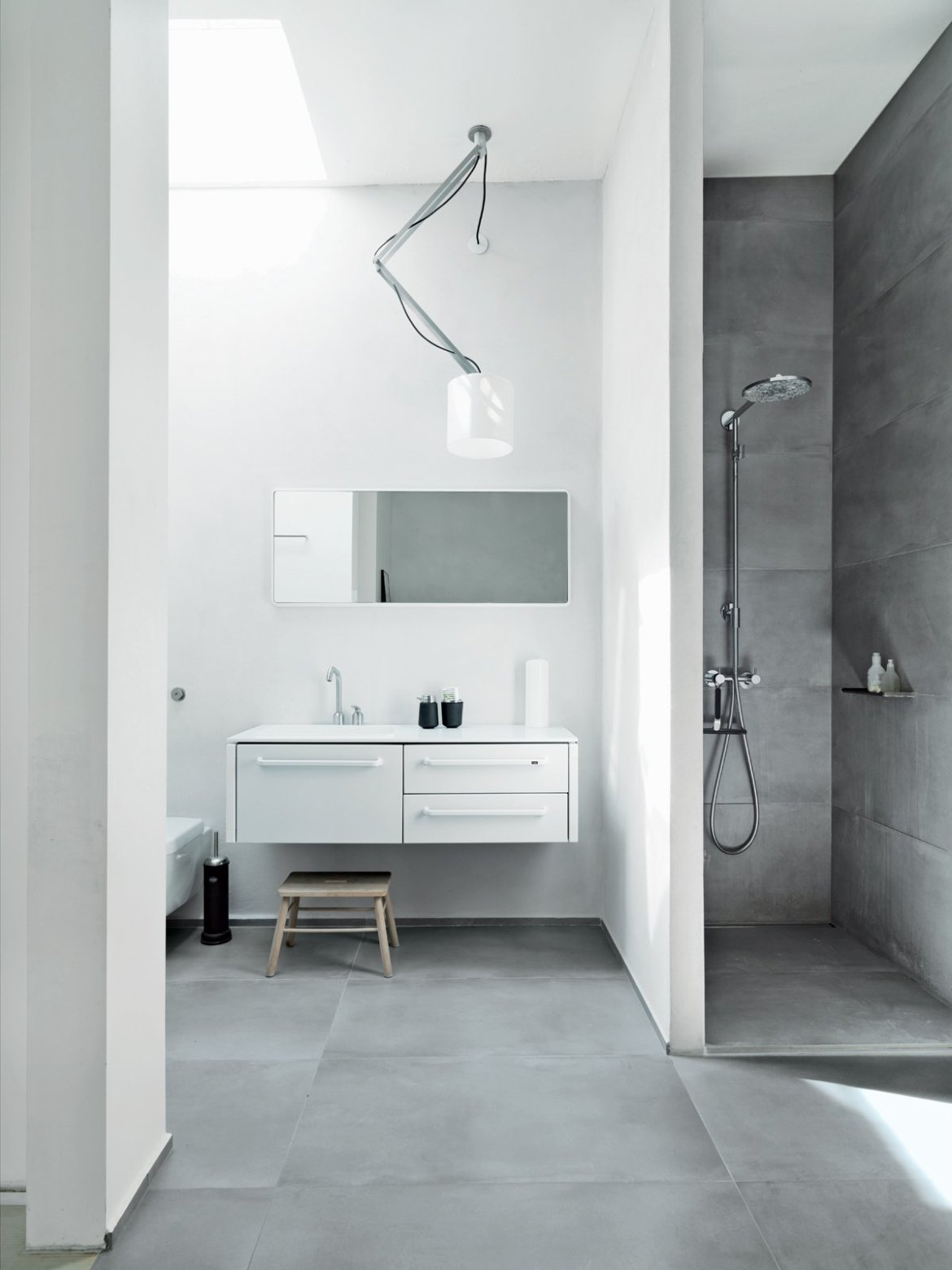 The resident family shares one main bathroom, which is outfitted with Vipp's line of products: 982 bath furniture, a 906 faucet, and a 992 mirror. The shower sports a Raindance Connect showerhead by Hansgrohe, and there is a wall-mounted toilet by Villeroy & Boch. The Nomad light fixture is from Modular Lighting Instruments, and the floors are topped with ceramic tiles by LaFaenza.