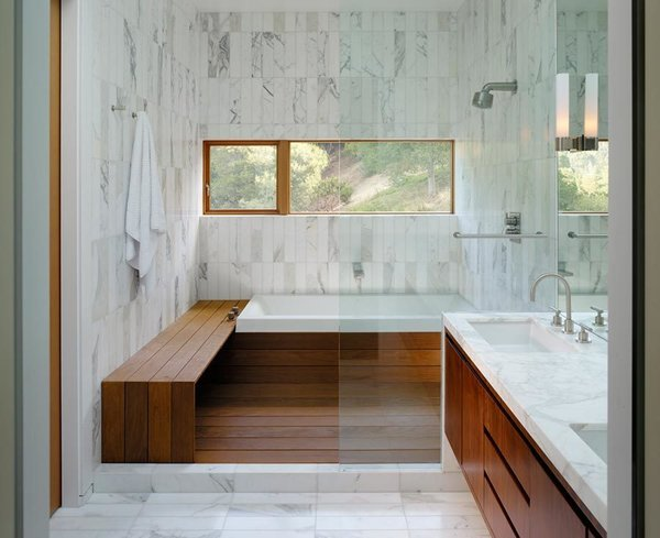 Wood meets white marble in this well-lit bathroom by architect Craig Steely. Contrasting materials make for a warm and serene bathing atmosphere in this Berkeley, California home.
