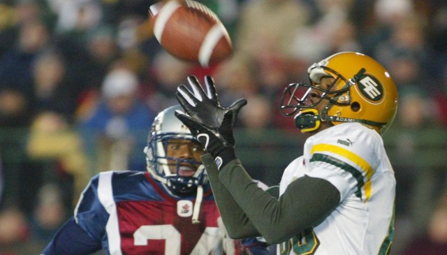 Edmonton Eskimos wide receiver Jason Tucker catches the pass for a touchdown ahead of Montreal Alouettes defensive back D.J. Johnson during second quarter CFL Grey Cup action Sunday, Nov. 16, 2003 in Regina. (CP PHOTO/Ryan Remiorz)