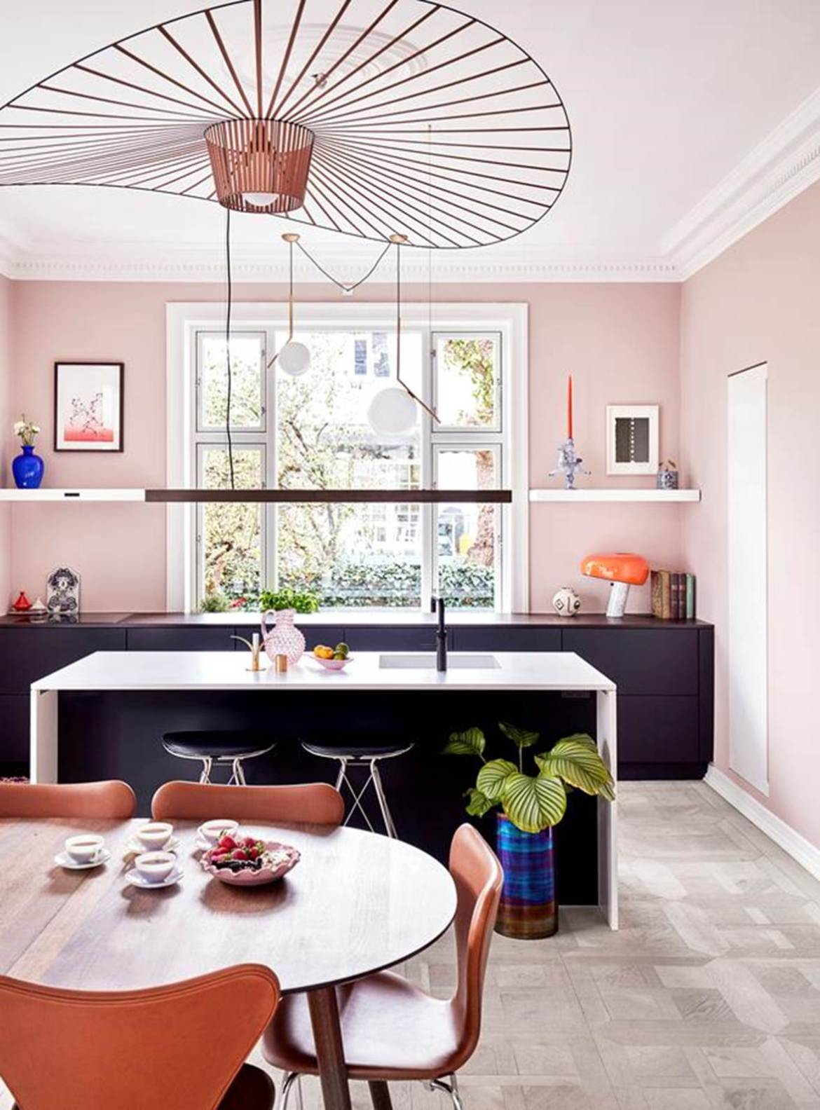 "A carefully chosen colour palette of pale pink, orange and deep blue are splashed throughout this charming kitchen in an [eclectic apartment](https://www.homestolove.com.au/colourful-eclectic-style-apartment-19184|target=""_blank"") in Frederiksberg, Denmark. The kitchen offers a wealth of colour, with black cabinetry and a low-hanging lamp to create contrast."