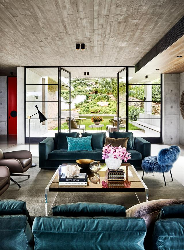 "Throughout this [modernist home](https://www.homestolove.com.au/a-modernist-home-with-a-maximalist-interior-6555|target=""_blank""), rich textures and pops of colour add warmth and interest. ""The living area is like a jewellery box, with the teal velvet sofas, the gold-leaf accessories and the rich, deep silk rug,"" designer Justine Hugh-Jones says. Sapphire blue chairs in the adjoining dining area heighten the effect."