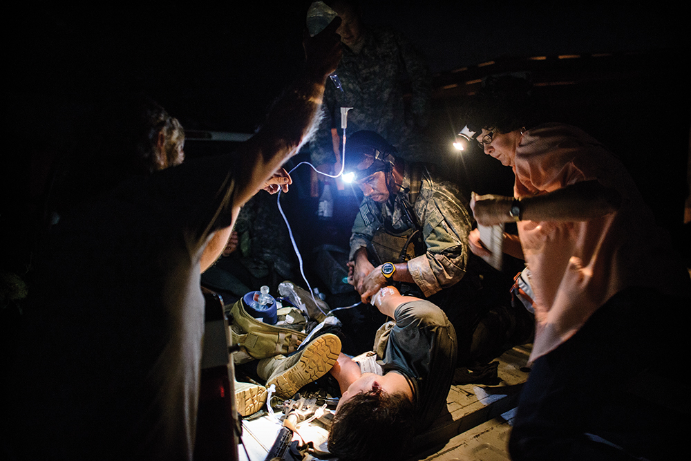 "A Special Forces student works on a ""wounded"" guerrilla with the help of local role-players at a makeshift hospital on Jim and Ann Nance's property during the Robin Sage exercise."