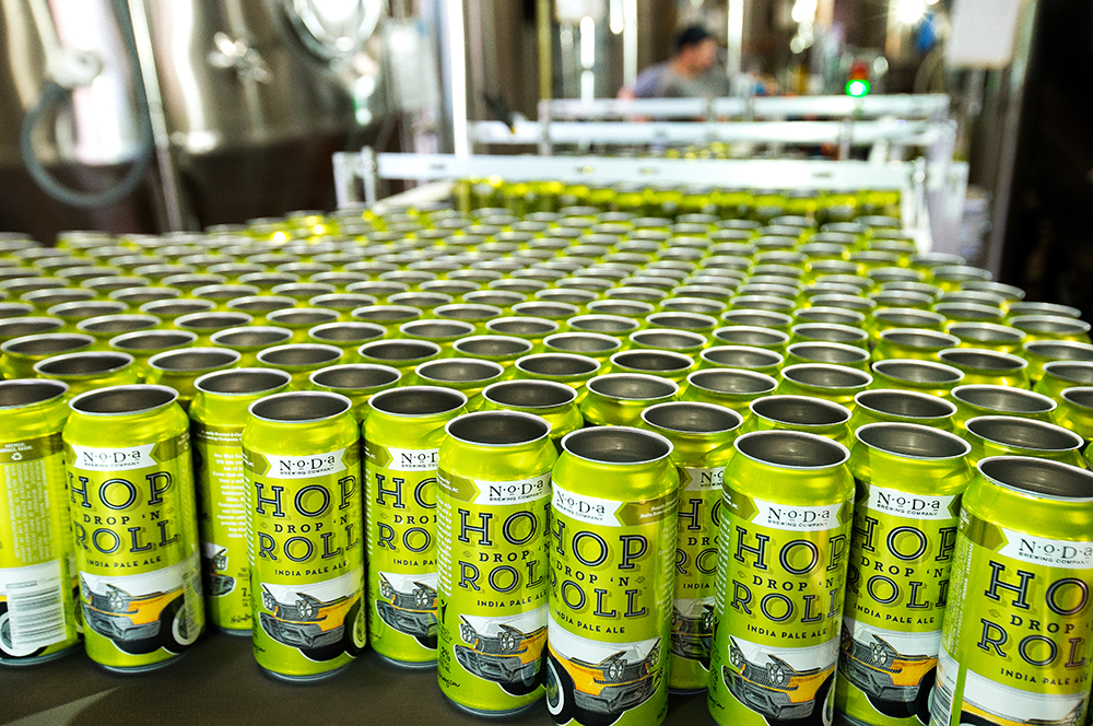 Empty cans wait to be filled with NoDa Brewing's IPA, Hop, Drop 'n Roll.