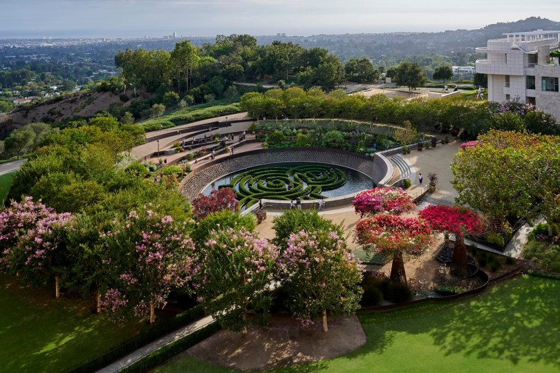 Birds-eye view of a round garden, pink trees and greenery