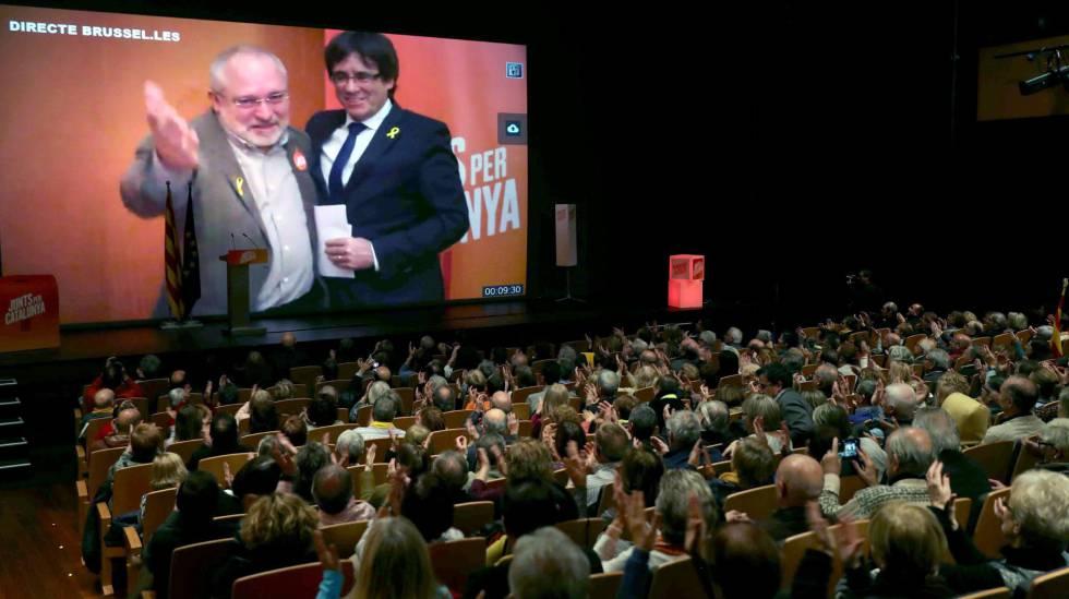 Carles Puigdemont y el exconseller Lluis Puig, en videoconferencia en un mitin de Junts per Catalunya en Terrassa.