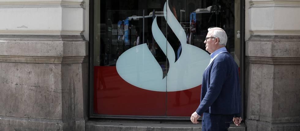 Un hombre pasando por delante de una oficina de Banco Santander
