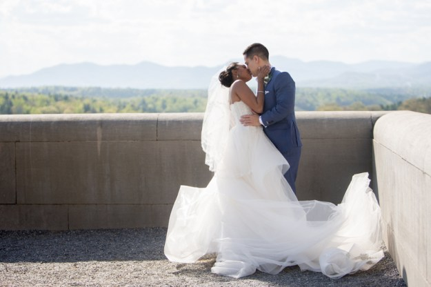 Bride and groom kissing on the balcony at the Biltmore Estate during their wedding with mountains in the background.