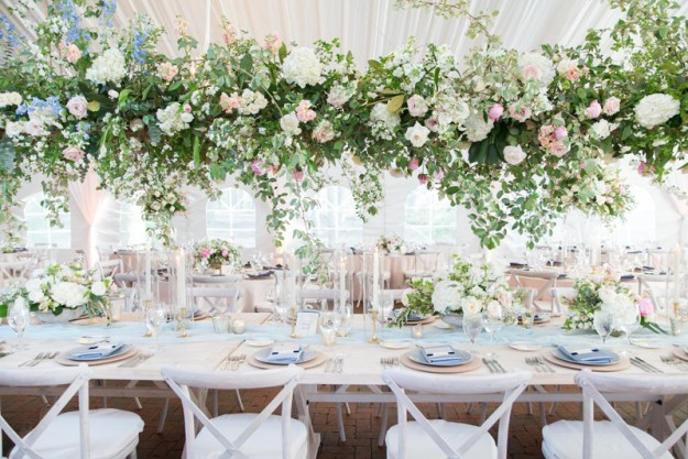 Pink, white and green floral chandelier  over wedding reception long tables