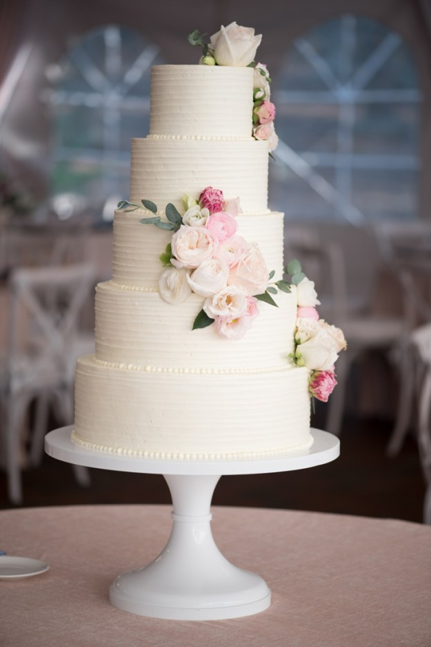 5 tier wedding cake with roses in varying shades of pink