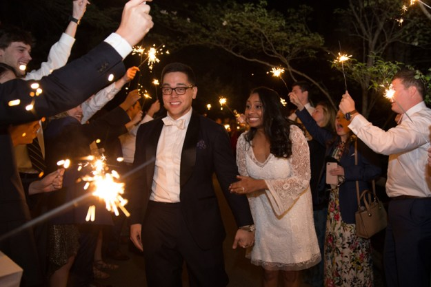 Bride and groom exiting wedding reception while guests hold sparklers and cheer.