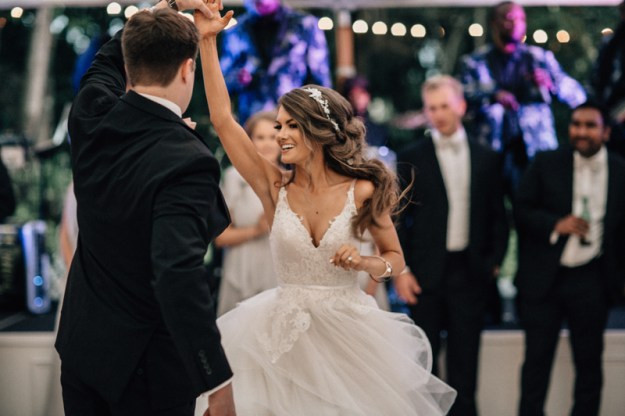 bride twirling on dance floor with band in background