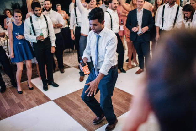 wedding guest in center of dance floor crowd showing off his dance moves