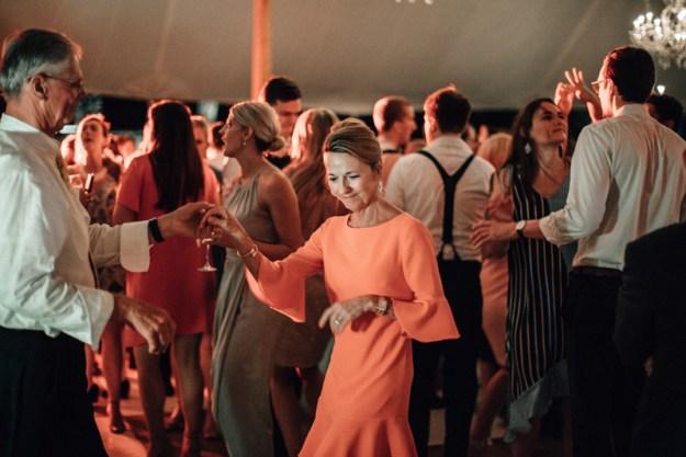 woman in orange dress dancing at wedding reception