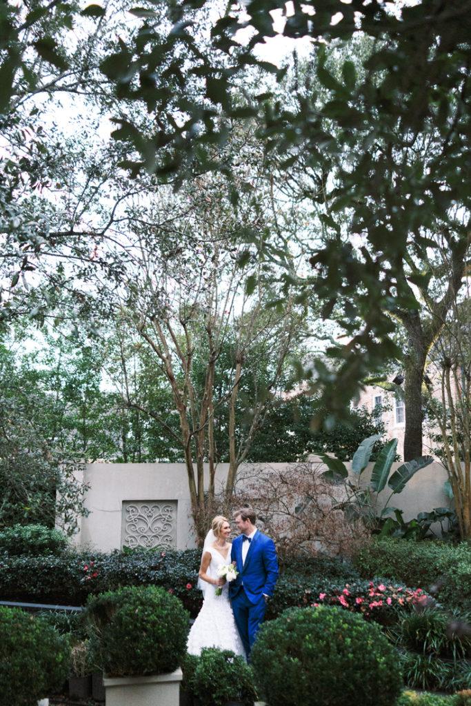 Bride and groom standing in middle of garden