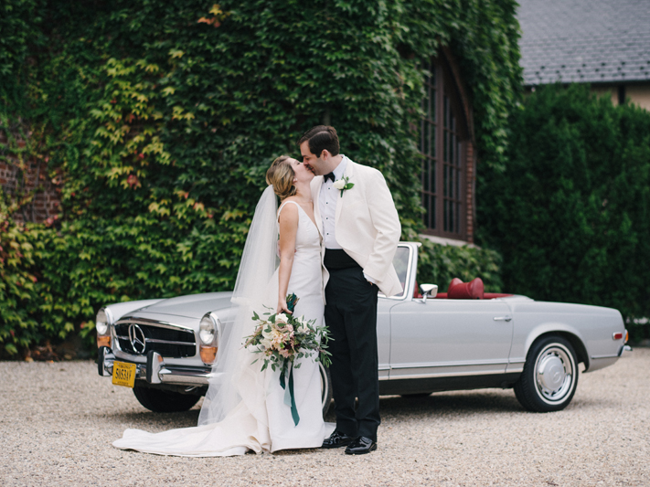 Bride and groom kissing in front of vintage car