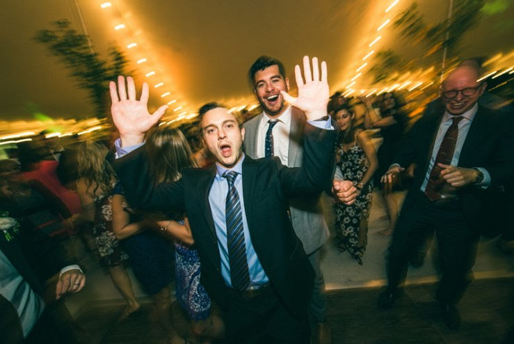 Man dancing with hands in the air during Summerfield Farms wedding reception.