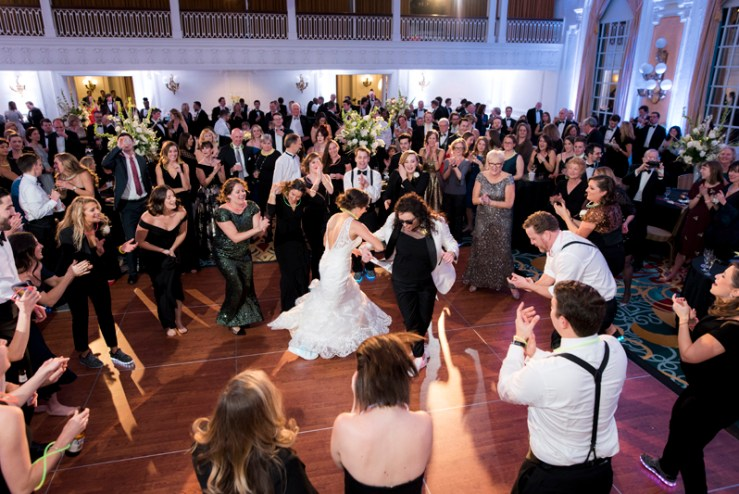 Two brides on dance floor surrounded by guests during their The Jefferson Hotel wedding.