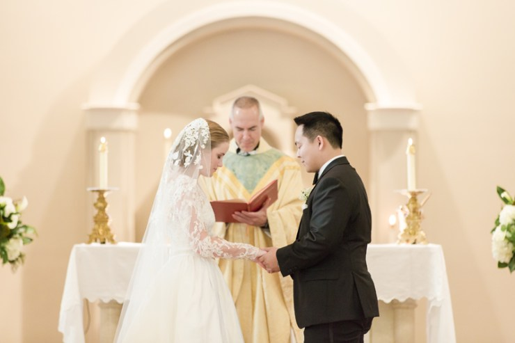 Bride and groom saying vows in front of minister during church wedding.