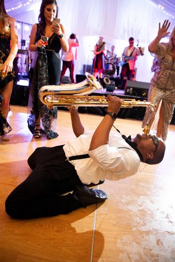 Sax player on dance floor during wedding reception at Biltmore Estate.