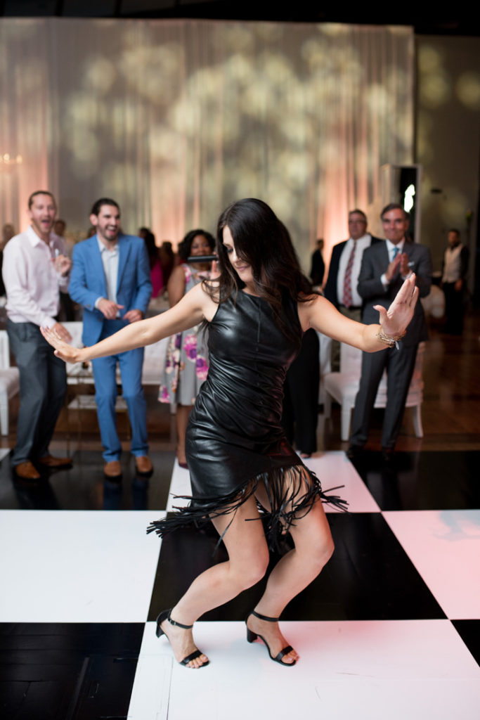 Woman in leather dress on dance floor at Nashville wedding.