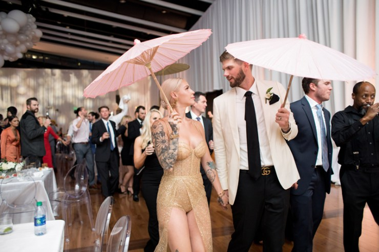 Bride and groom with pink and white parasols in Second Line at Nashville wedding.