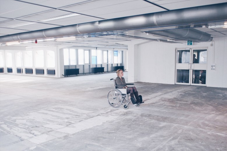 One member of the five participants walks into the space and sits down in a wheelchair while te rest stays behind