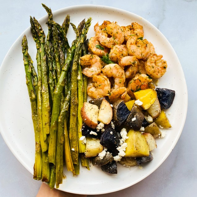 Full photo of greek shrimp sheet pan meal of asparagus, shrimp, and mixed color potatoes with feta on a white plate and white background.
