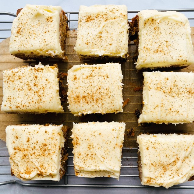 Squares of carrot cake bars with cream cheese frosting on top of a wire baking rack and white background.