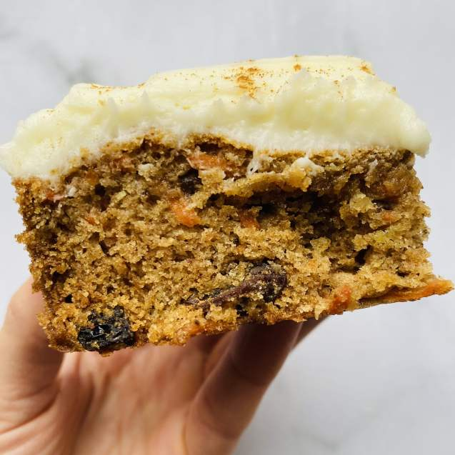 Close up shot of one slice of carrot cake bars with cream cheese frosting against a white background.