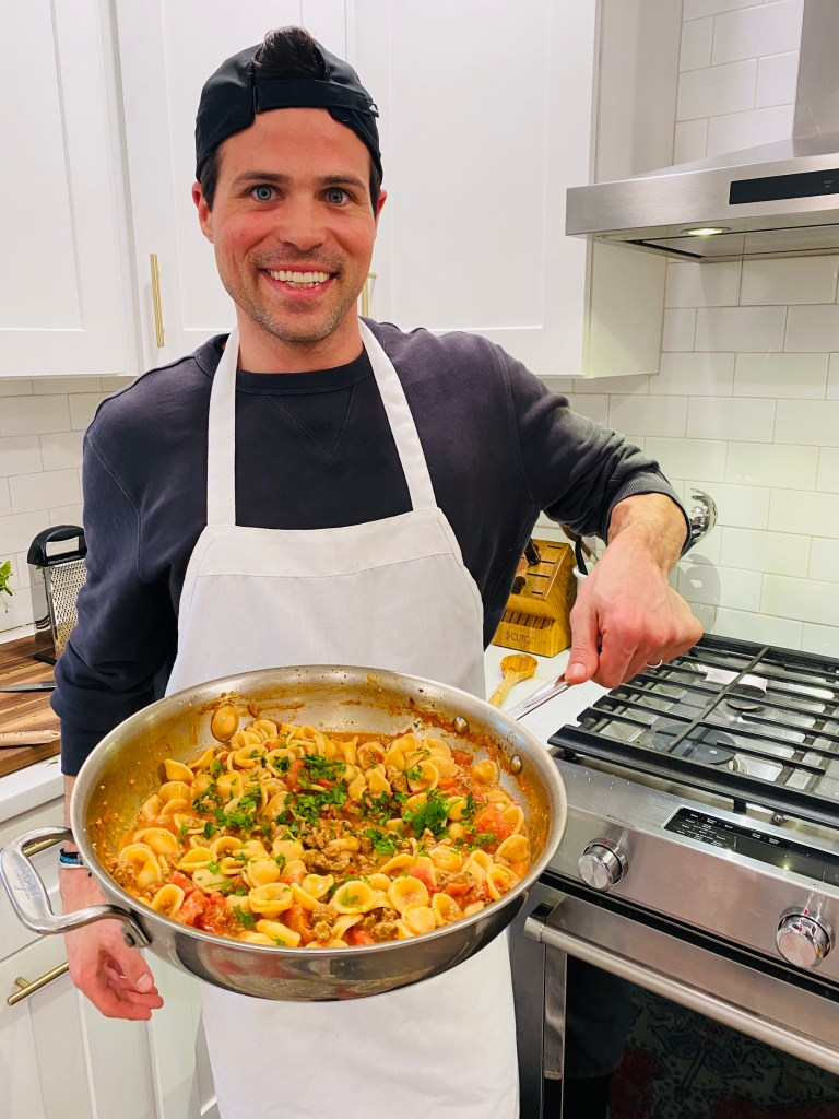 Thomas (or man) wearing apron holding pan filled with Orecchiette Pasta with Italian Sausage with kitchen in the background.