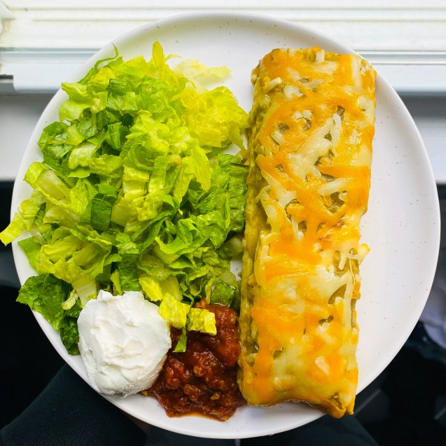 White plate topped with a green chili chicken enchilada, romaine, salsa, yogurt against a dark background with a hand holding the plate.