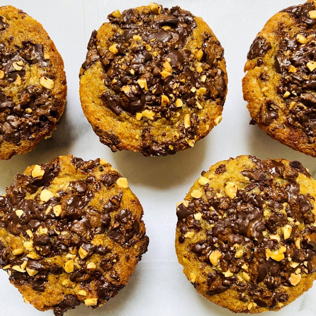 Five chocolate chip banana bread muffins topped with melted peanut butter chocolate on a white background.