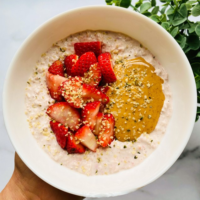 White bowl full of strawberry cheesecake overnight oats topped with strawberries, peanut butter, and hemp seeds against a white background with a green plant in the top right corner.