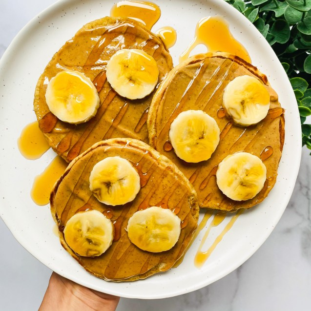 Three sourdough pancakes topped with banana, peanut butter, and maple syrup on a white plate with a hand holding on white background and green plant in top right corner.