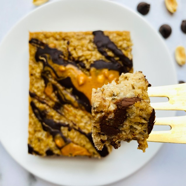 Slice of peanut butter cup baked oatmeal on a white plate with a close up of a bite and peanuts and chocolate chips in the top right corner.