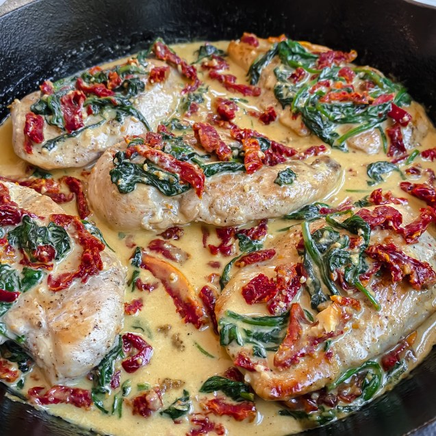 Side view of creamy tuscan skillet chicken in a cast iron with creamy sauce topped with spinach and sundried tomatoes.