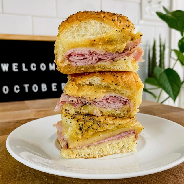 Three ham & cheese sliders stacked on top of each other on a white plate with a black sign in the left corner and a green plant in the right corner.